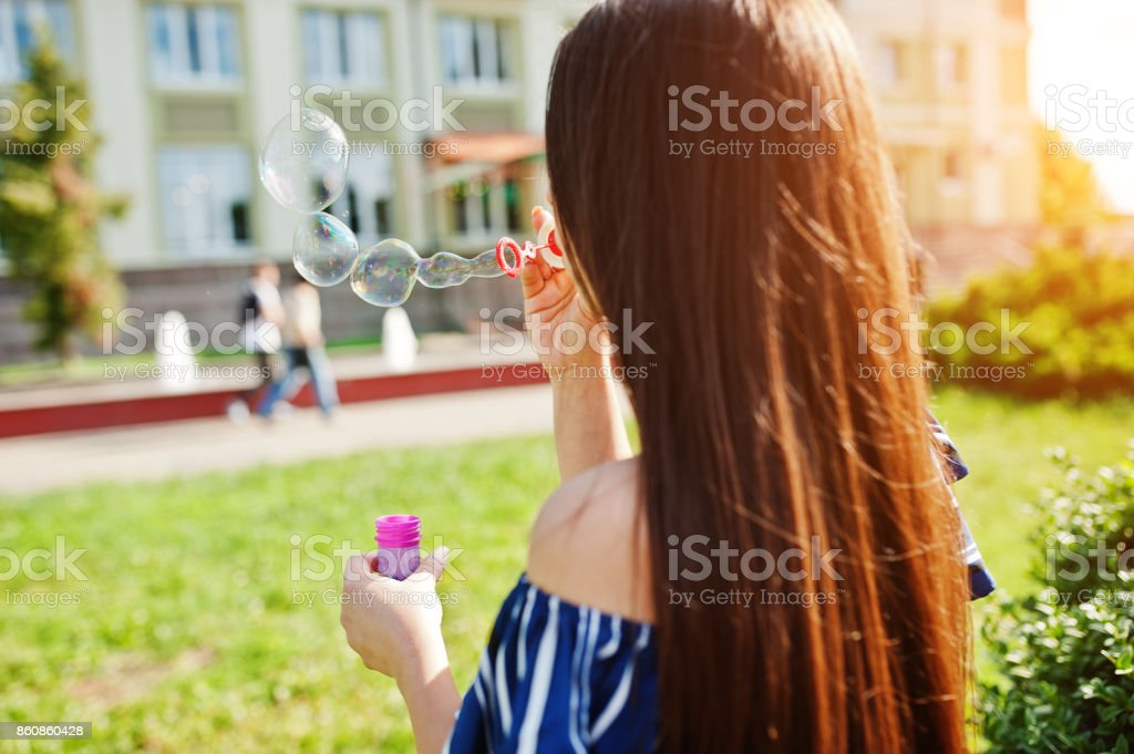 Gorgeous brunette girl at street of city lets out soap bubbles. stock photo