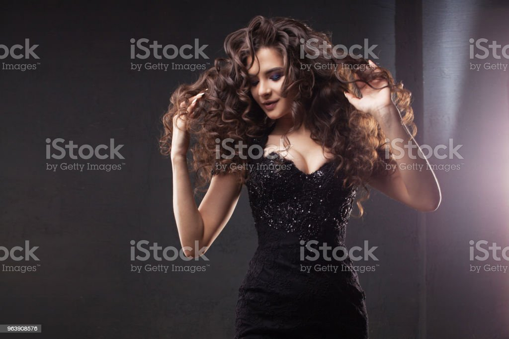 Gorgeous brunette girl in elegant black dress. Beautiful long curly hair. - Royalty-free Beauty Stock Photo