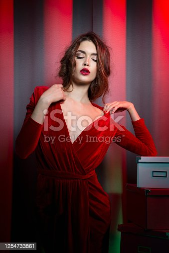 Sensual brunette woman in elegant velvet red dress with decolletage, with hairstyle and makeup, posing in studio at the red neon background.