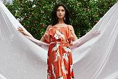 リンゴ園でのファッション オレンジのドレスでゴージャスなブルネットの女性