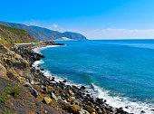 Gorgeous California Pacific Coast Highway mountains meet crashing waves of aqua blue ocean