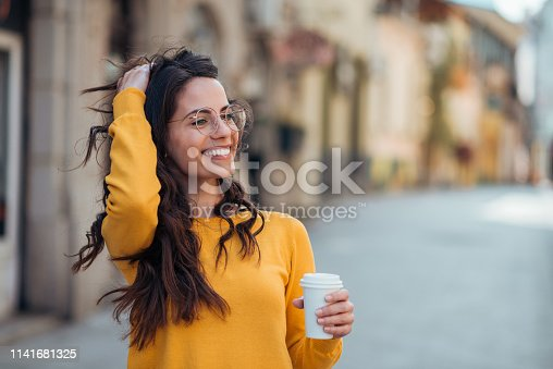Gorgeous casual brunette in the town street, smiling and drinking coffee to go.