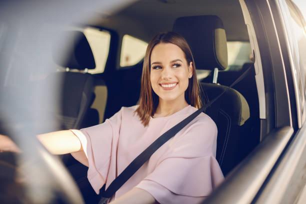 brunette caucasiano lindo com o sorriso toothy grande que conduz o carro. mãos no volante. - carro mulher - fotografias e filmes do acervo