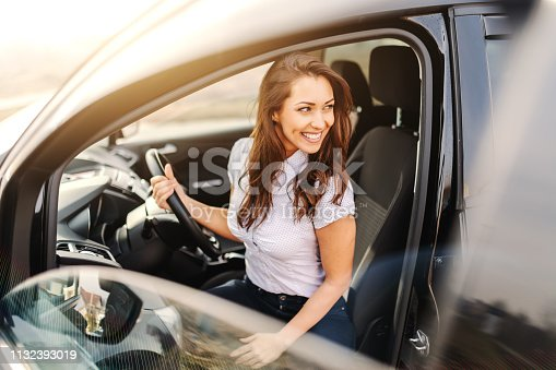 istock Gorgeous Caucasian woman with brown hair and toothy smile getting out of car. 1132393019