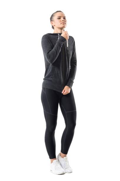 umwerfende zuversichtlich sportliche frau zipping zip up sweatshirt mit kapuze blick in die kamera - zip hoodies stock-fotos und bilder