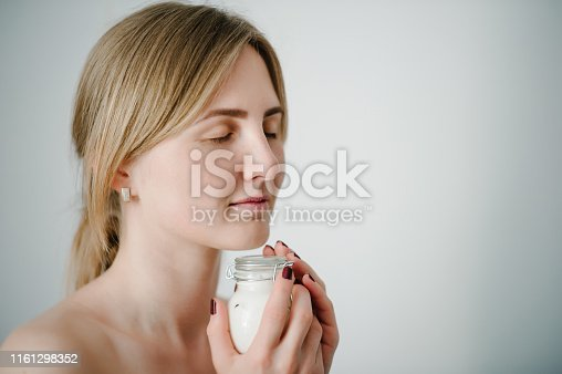 532331272 istock photo Gorgeous cute pretty charming blonde girl holding bottles of moisturizing cream on her face. Woman caring of her beautiful skin on the face natural cosmetics. Place for text and advertising. 1161298352