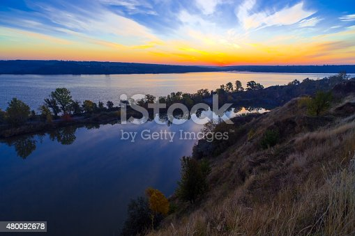 River with island in the middle with forest terrain and colourful majestic sunrise