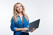Favorite device. Beautiful fair-haired young woman in a denim shirt posing with a laptop while standing isolated on a white background
