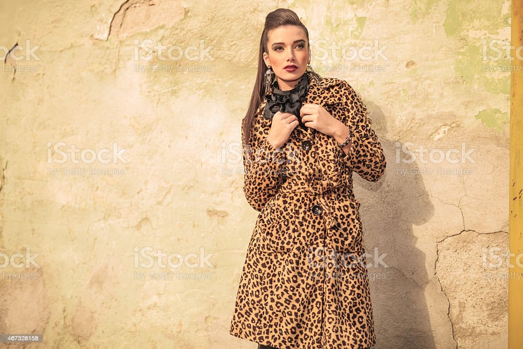Gorgeous fashion woman fixing her coat stock photo