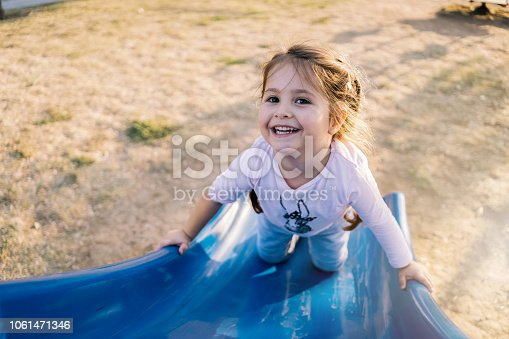 Lovely and carefree child enjoying her day at a park, playing on a slide at a playground.