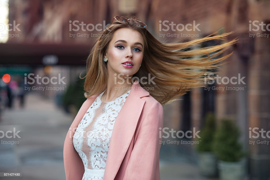 Gorgeous girl with long hair blowing in wind in city stock photo