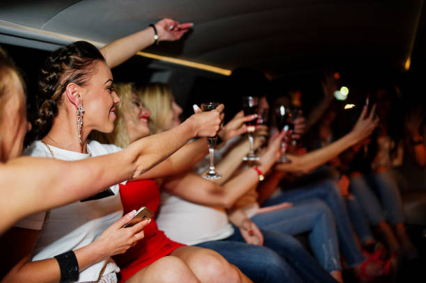Gorgeous girls having fun and drinking while sitting inside the luxurious limousin at bachelorette party. stock photo