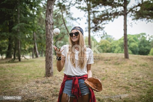 Handsome and retro looking girl, having fun with a baseball and a baseball glove in a forest.