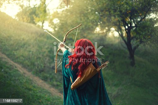istock gorgeous huntress pushing her last light to the sun, waiting for salvation during terrible danger, red-haired girl fights for life, emerald velvet cloak, photo without a face from the back 1168155217