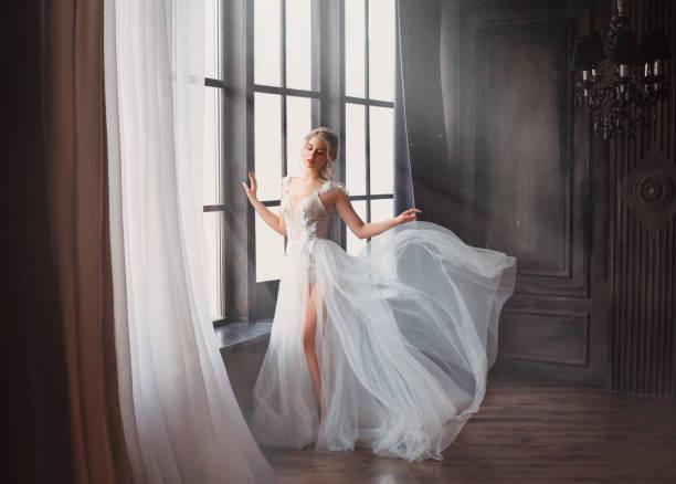 wunderschönes bild des absolventen im jahr 2019, mädchen in langem weißem licht sanfte fliegende kleid mit nacktem bein steht allein, schwanen-prinzessin vor der aufführung auf ballettbühne, elegante dame mit blonden haaren im sonnenlicht - festliche kleider kindermode stock-fotos und bilder