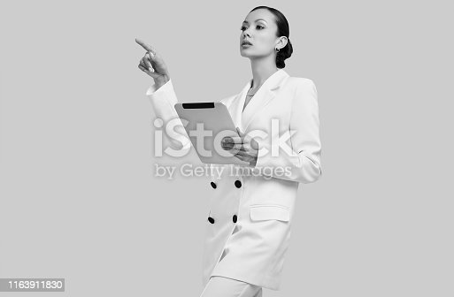 Portrait of a cute and gorgeous latin women in fashion white suit with digital tablet posing on bright studio background