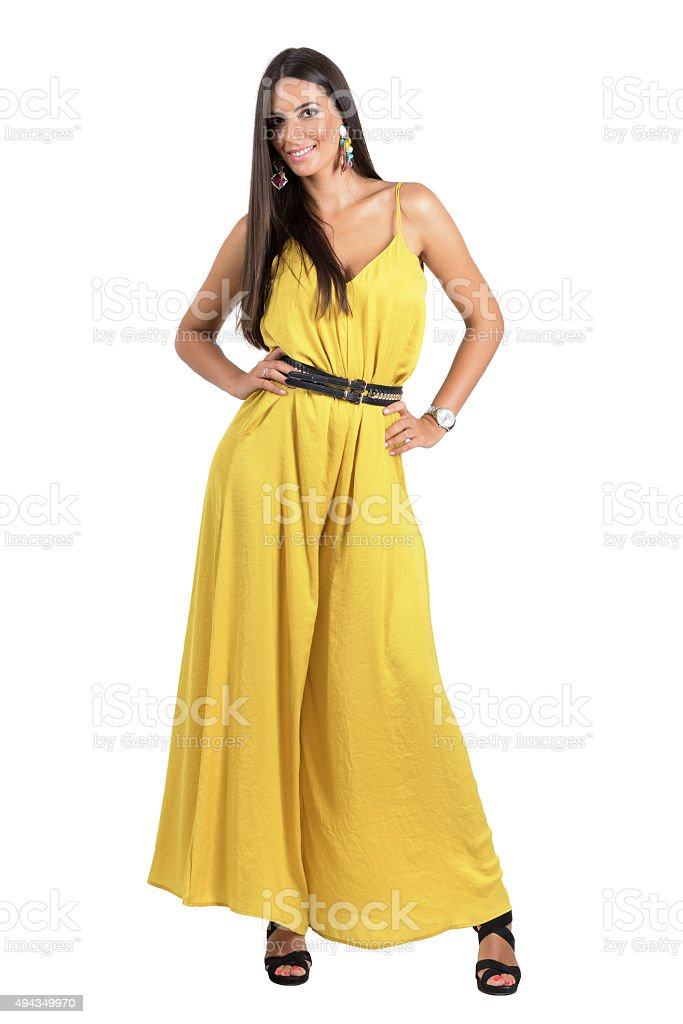 Gorgeous Latino fashion model in ocher jumpsuit posing to camera. stock photo