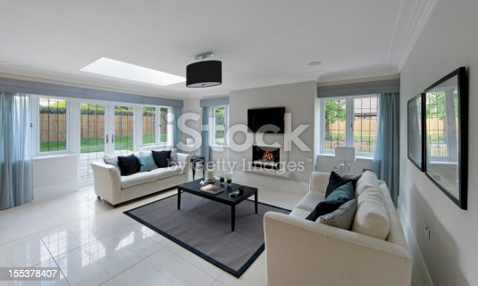 a gorgeous lounge in an expensive new home with two cream coloured settees on either side of a coffee table with a lit gas fire in the background. Subtely decorated with light blue drapes and matching cushions. The copyright for the book design belongs to the photographer.