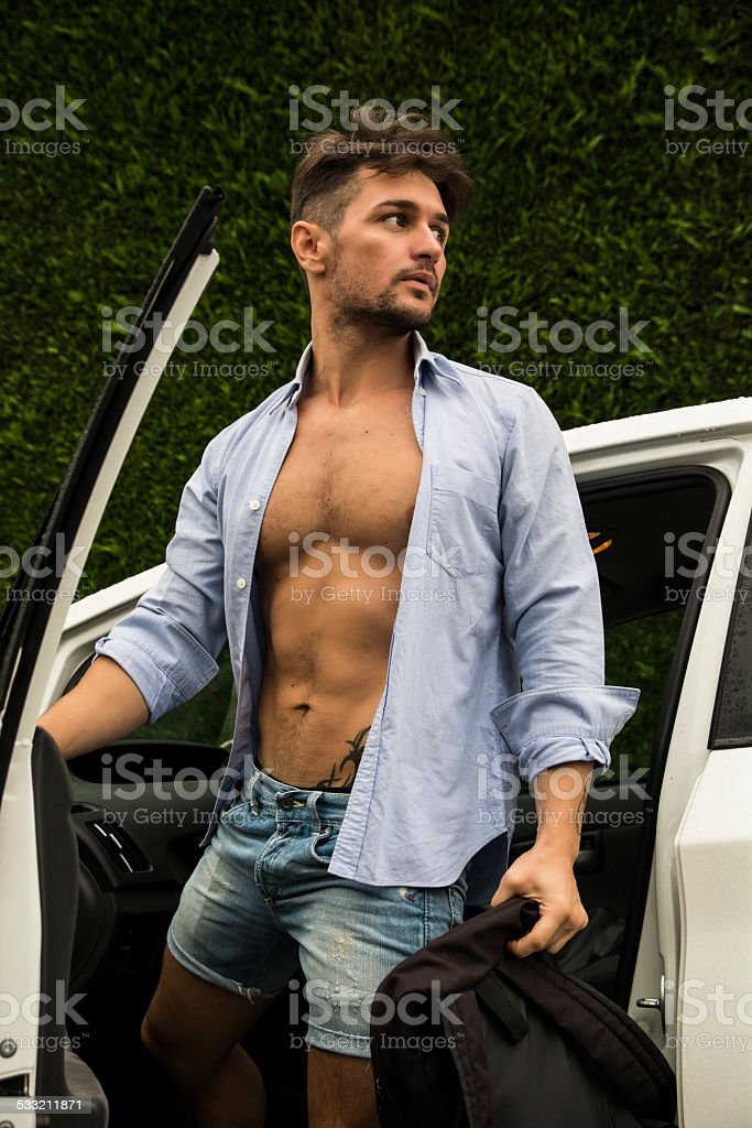 Gorgeous Man in Beach Attire Getting Out his Car stock photo
