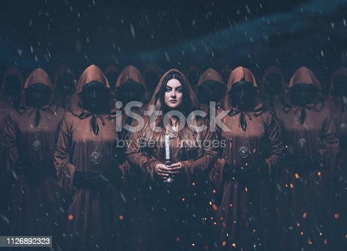 A girl servant wanders around with candles. A crowd of people in masks wearing robes. Creative color. gorgeous mysterious priestess standing in a group,brown cloaks and hoods