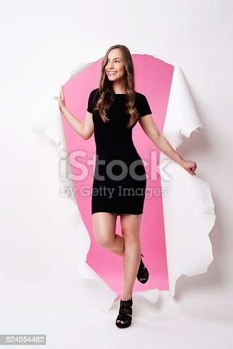 istock Gorgeous model emerging from torn paper, smiling 524554482