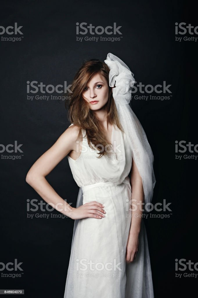 gorgeous modern bride standing in wedding dress and'r'nveil stock photo