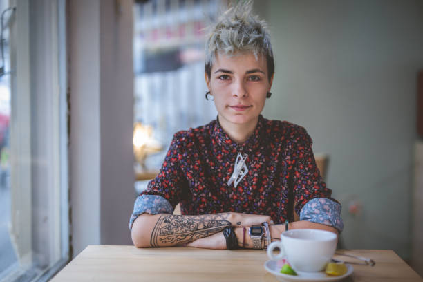 Gorgeous modern woman Young and lovely gender blend woman, enjoying a cup of coffee at the cafe. lgbtqi rights stock pictures, royalty-free photos & images