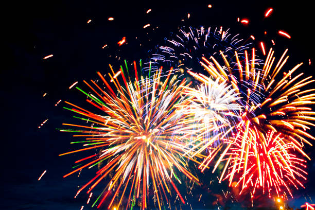 Gorgeous multi-colored fireworks display on dark background stock photo