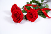 istock Gorgeous red roses on a white isolated background with a gift ribbon. Best gift for mother's day and Valentine's day 1284128107