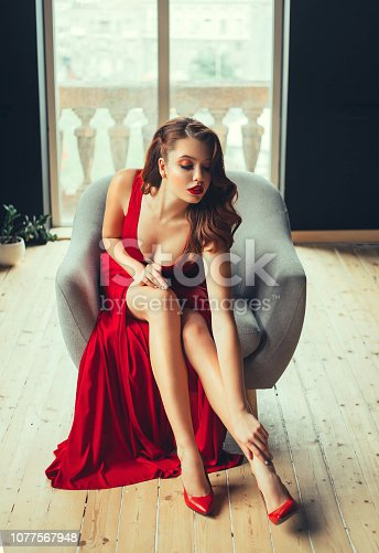 172214590istockphoto gorgeous red-haired young woman sexually touches her bare leg, showing the neckline. in a long scarlet expensive long luxurious dress and red high-heeled shoes in a room with window to the floor 1077567948