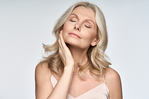 Gorgeous senior older woman with closed eyes touching her perfect skin. Beautiful portrait mid 50s aged woman advertising facial antiage lift products salon care tighten skin isolated on white.