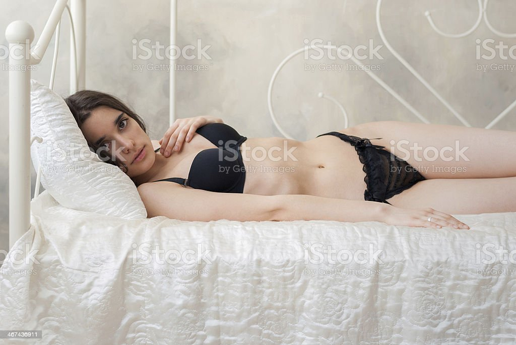 Gorgeous slim girl in lingerie lying on a bed stock photo
