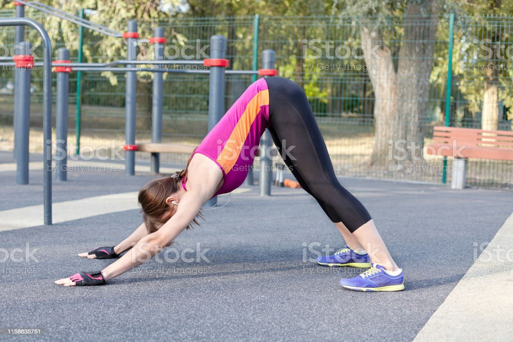 Gorgeous slim young woman practices yoga at outdoor sportsground....