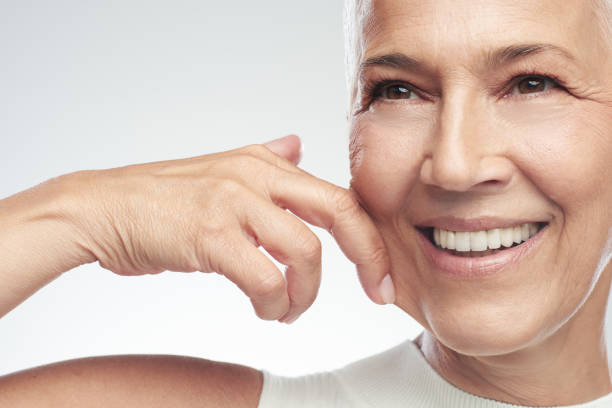 Gorgeous smiling Caucasian senior woman with short gray hair pinching her cheek. Beauty photography. stock photo