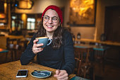 Gorgeous smiling hipster girl at a coffee shop