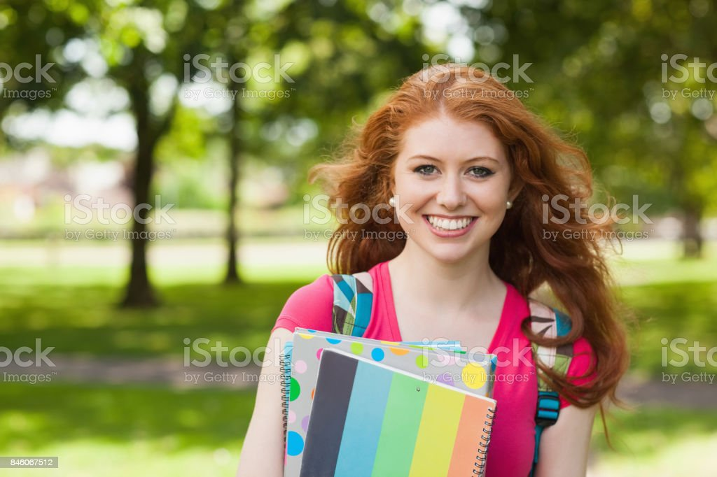 Gorgeous smiling student holding notebooks stock photo