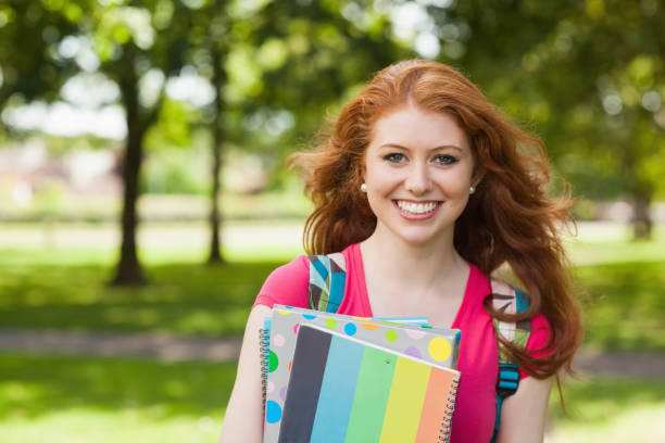 Gorgeous smiling student holding notebooks Gorgeous smiling student holding notebooks on campus at college 18 19 years stock pictures, royalty-free photos & images