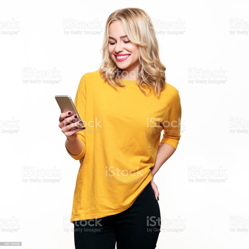 Hermosa mujer sonriente mirando su teléfono móvil. Mujer enviar mensajes de texto en su teléfono, aislado sobre fondo blanco. foto de stock libre de derechos