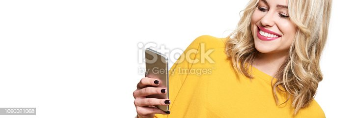 640046924 istock photo Gorgeous smiling woman looking at her mobile phone. Woman texting on her phone, isolated over white background. Banner with copy space. 1060021068