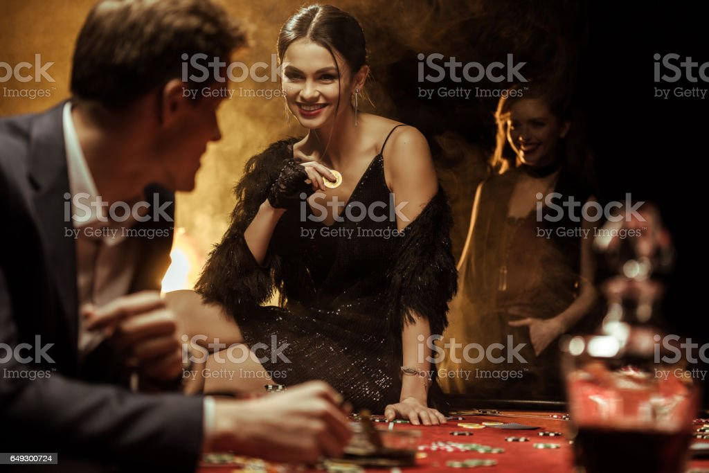 Gorgeous smiling woman with casino chip sitting on poker table stock photo