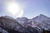 An image I took this year in Oberstdorf (Bavaria, Germany). The beautiful lens flare stays in contrast with the astonishing black and white mountains. Further, this image represents the idyllic feeling of going on vacation in the Alps during winter.