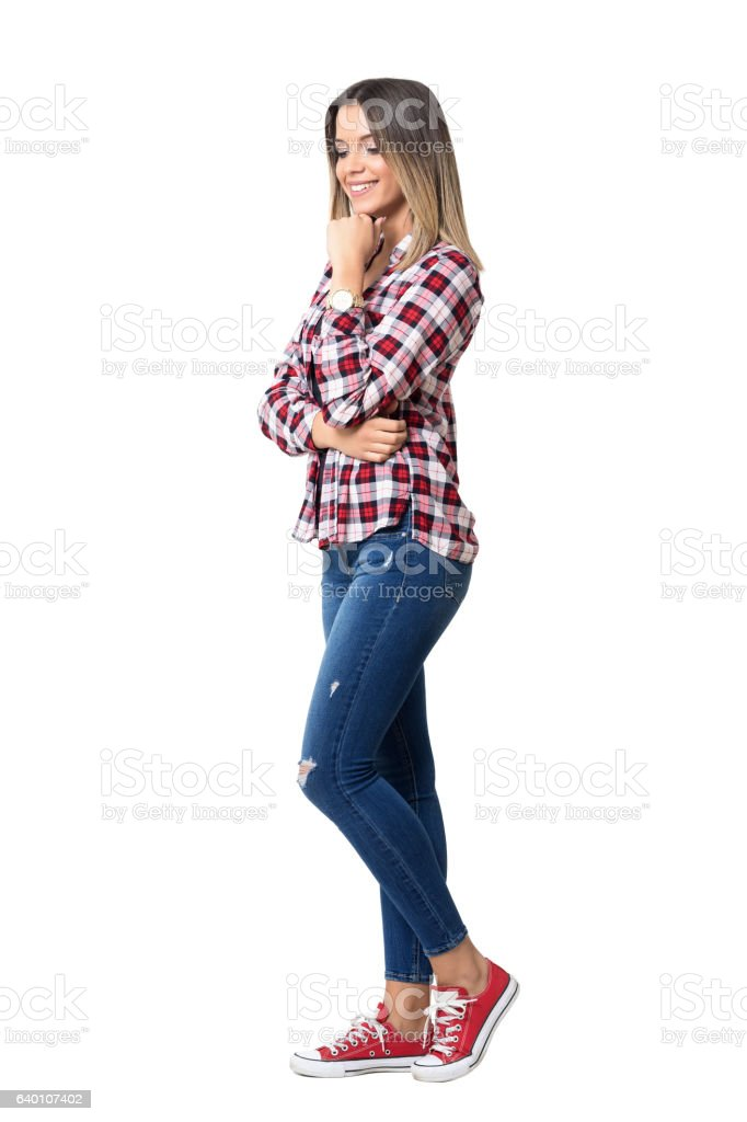 Gorgeous street style woman wearing jeans, plaid shirt and sneakers stock photo