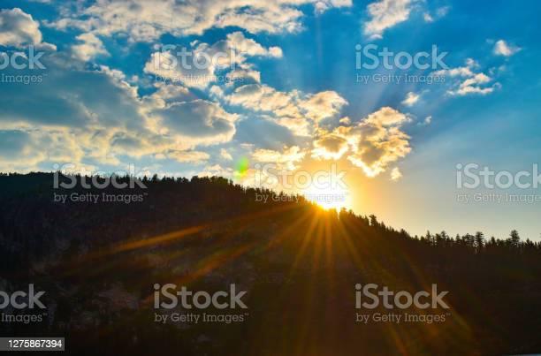 Photo of Gorgeous sun rays beam across mountains under bright blue sky
