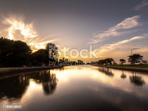 A gorgeous sunset, clouds and trees reflecting on the calm water of the South Lagoon in Lincoln Park in Chicago as people begin to gather in the park and shoreline for an event later in the day.