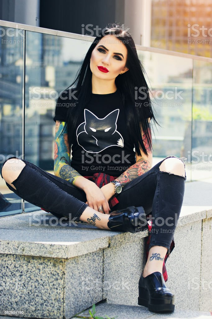 Gorgeous tattoed woman. Portrait of young tattooed hipster girl posing against urban background. foto de stock royalty-free