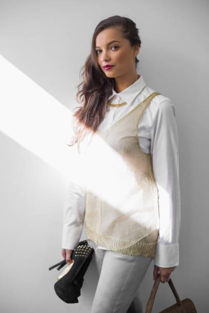 wunderschöne trendige frau mit high heels und handtasche - pflaumen jeans stock-fotos und bilder