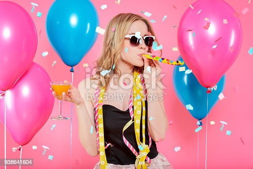 istock Gorgeous trendy young woman in party outfit celebrating birthday. Party mood, balloons, noisemaker, flying confetti, cocktail and dancing concept on pastel pink background. 938641604