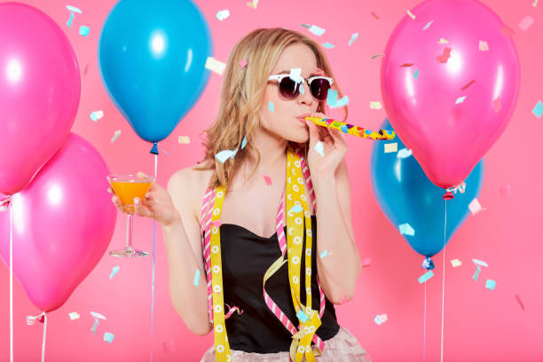 Gorgeous trendy young woman in party outfit celebrating birthday. Party mood, balloons, noisemaker, flying confetti, cocktail and dancing concept on pastel pink background. stock photo