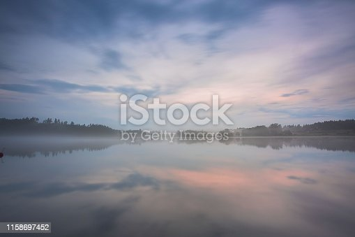 Gorgeous view of fog on sunset on lake on summer day. White clouds on blue sky. Europe. Sweden. Gorgeous backgrounds.