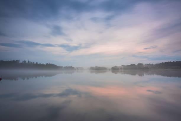 vacker utsikt över dimman vid solnedgången på sjön under sommar dagen. vita moln på blå himmel. europa. sverige. underbara bakgrunder. - nature foggy calm bildbanksfoton och bilder